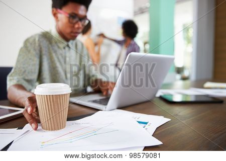 Close Up Of Businessman Reaching For Cup Of Coffee In Office