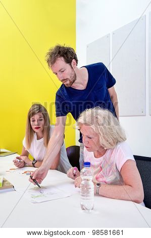 Art teacher gives instructions to his students in a creative studio to two students in a master class product design and development.