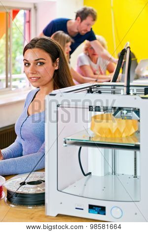 Young woman, standing next to a 3D printer at a rapid prototyping design firm, with several people working in the background