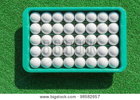 The New Golf Balls In Tray On Green Grass For Golf Practice.