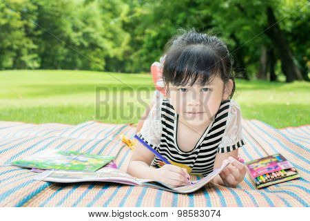 Young girl outdoors lying on the grass and drawing