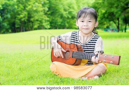 Asian Kids Sitting On Grass And Play Ukulele In Park