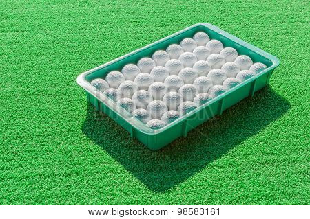 White Golf Balls Contrasting With Green Grass Background.