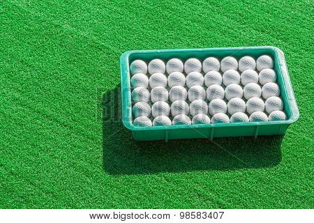 Rows Of Golf Balls In Tray On Green Grass.