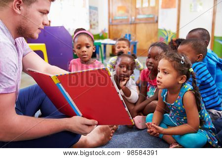 Volunteer teacher reading to a class of preschool kids