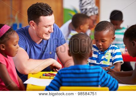 Volunteer teacher sitting with preschool kids in a classroom