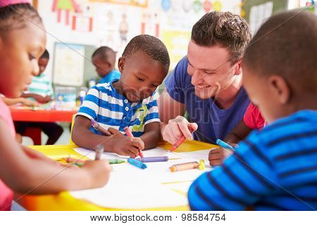 Volunteer teacher helping a class of preschool kids drawing