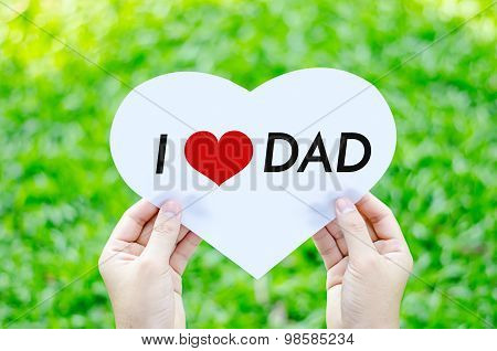 Hand Holding White Heart Paper With I Love Dad Text On Blur Green Grass Background