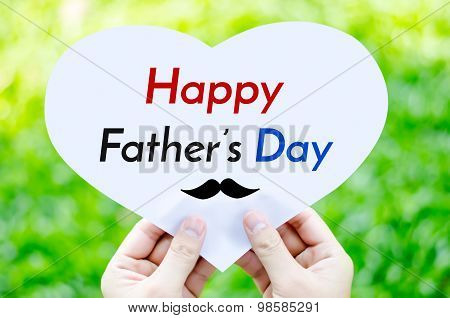 Hand Holding White Heart Paper With Happy Father's Day Text On Blur Green Grass Background