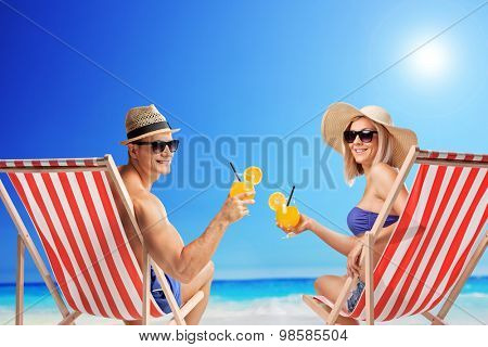 Young man and woman sitting on sun loungers and holding cocktails at a sunny beach