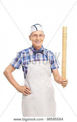 Vertical shot of a senior with a white cap and apron holding a huge vertical row of ice cream cones and looking at the camera isolated on white background