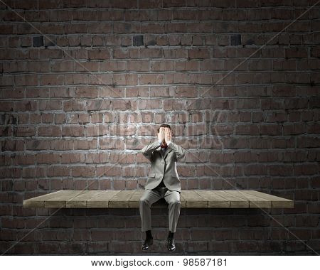 Young shocked businessman sitting on stone and covering eyes with palms