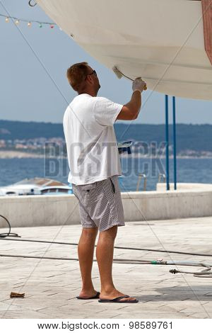 Man painting a boat