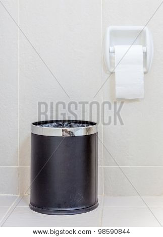 Toilet Paper And  Trashcan In White Hygeine Restroom.