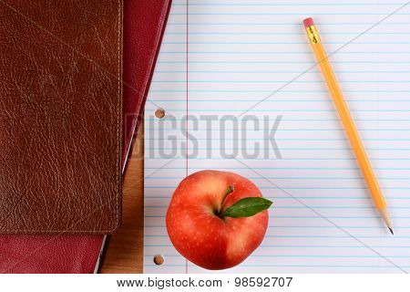 Overhead view of an apple  and pencil on notebook paper with school books. Closeup in horizontal format. Back to School concept.