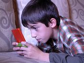 stock photo of video game  - a young boy playing a handheld video game - JPG