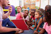 Volunteer teacher reading to a class of preschool kids poster
