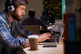 pic of late 20s  - Office Worker With Coffee At Desk Working Late On Laptop - JPG