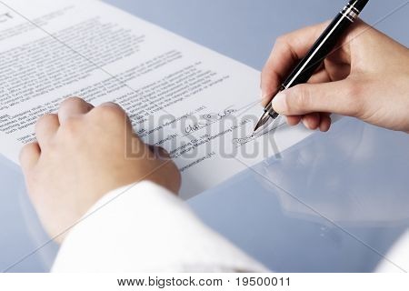Close up of woman signing a legal document or contract, blank background.