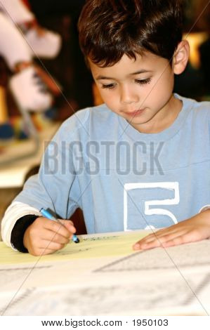 Young Boy Drawing With Blue Crayon