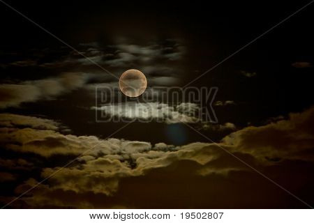 Image of the Moon in a cloudy night sky.