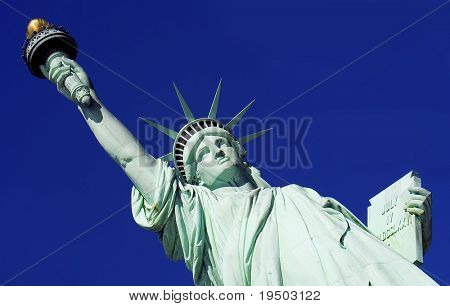 Close-up of Statue of Liberty against a bright blue sky.