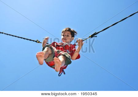 Young Boy In Trampoline Jumping Rope