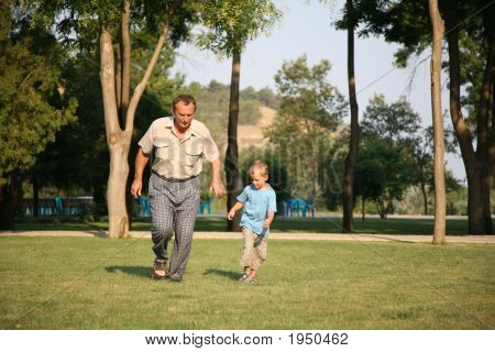 The Grandfather And The Grandson On A Meadow