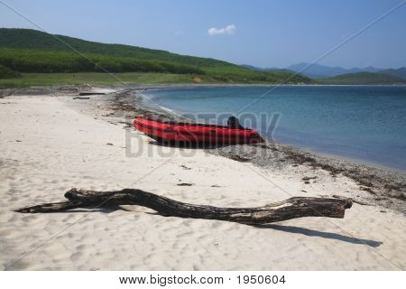 Red Rubber Boat On Isolated Sand Beach Under Blue Sky