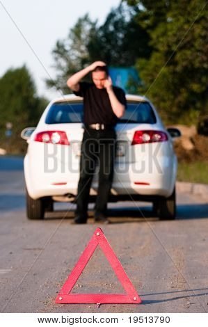 Young man calls to a service standing by a white car. Focus is on the red triangle sign