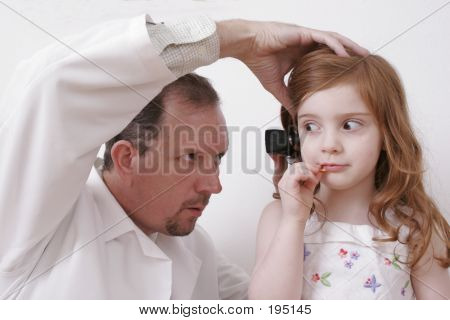 Doctor Looking In Little Girl's Ear