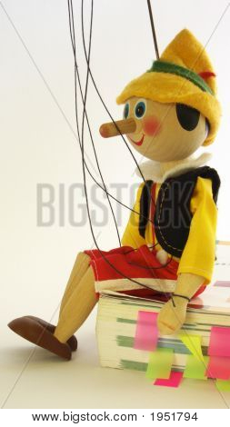 Wooden Puppet Sitting On The Book