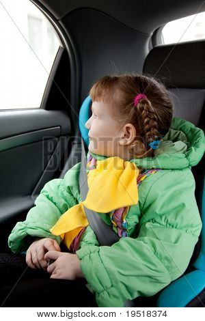 Cute little girl in the car. Traveling with safety.