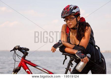 Junge Frau im Fahrradhelm, stehend mit dem Fahrrad, Flasche Wasser halten.