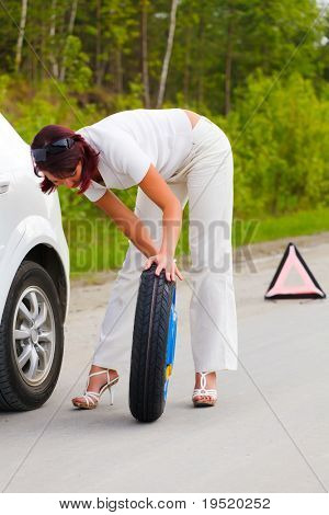 Woman trying to change the wheel.