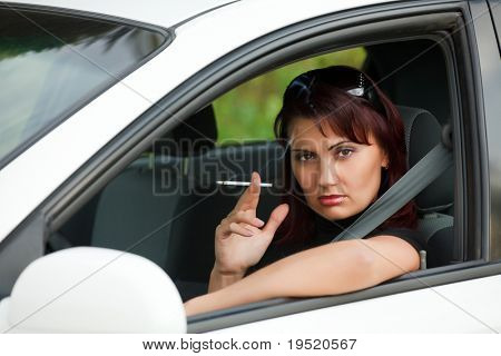 Pretty adult woman sitting in a car and smoking a cigarette