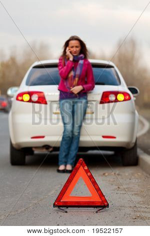Woman calls to a service standing by a white car. Focus is on the red triangle sign. Evening light.