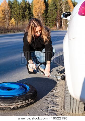 Young woman and the car with deflated wheel.