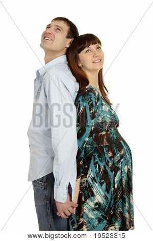 Husband and pregnant wife are standing and leaning on each other back. Isolated on white background.