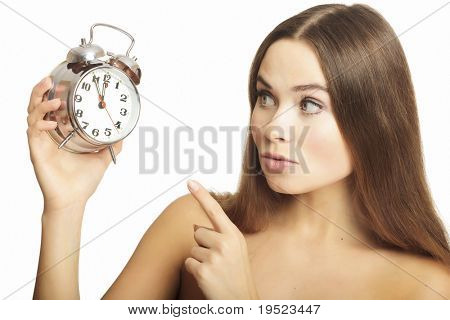 Portrait of the girl showing a finger on an alarm clock, isolated on white background.