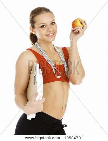 Sports woman holding an apple and carrying a weight scale, isolated on white background