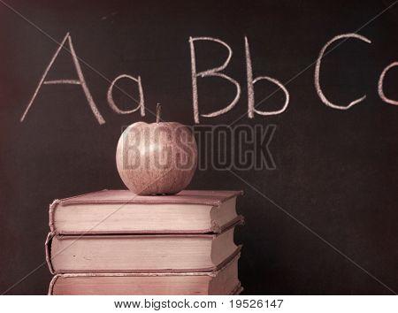 apple, textbooks, and ABC on a blackboard - sepia toned