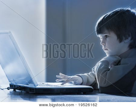 young boy concentrates on laptop computer - blue tone/b&w