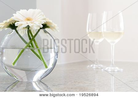 white daisies in vase with glasses of white wine in background