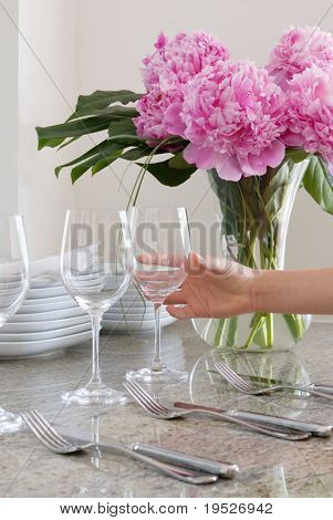hand places wine glass at elegant table