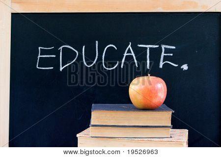 """EDUCATE"" written on chalkboard with red apple & books"