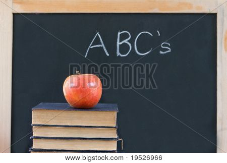 "Education: ""ABC's"" written on chalkboard with apple & books"