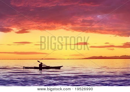 silhouette of man on kayak with sunset