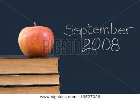 September 2008 written on blackboard with apple, books