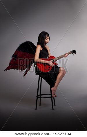 young woman in black dress & black angel wings plays guitar